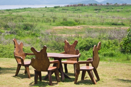 Wooden table and chairs in grassland photo