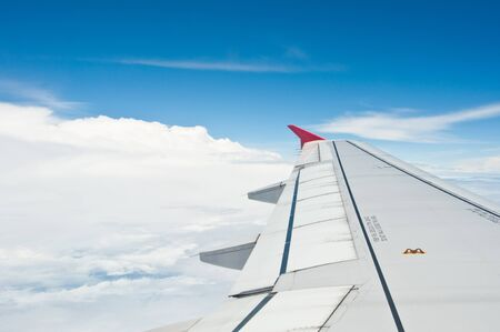 Airplane wing in the blue sky with white clouds  photo