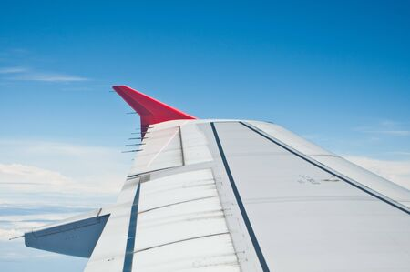 get away: Airplane wing with white cloud and blue sky