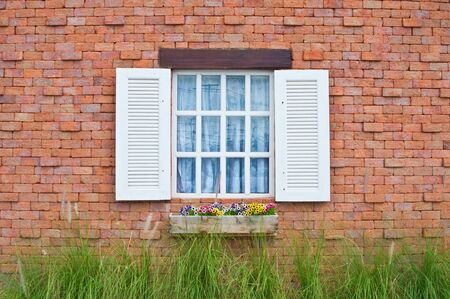 White window and red brick wall of house  photo