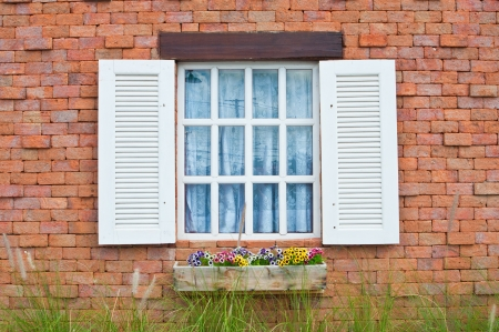 paint house:  White window on red brick wall of vintage house style Stock Photo