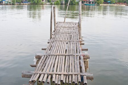 Old bamboo bridge on the lake photo