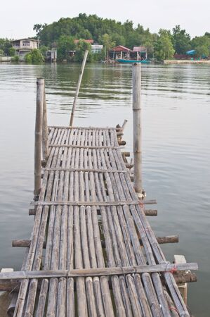 Old bamboo wooden bridge on the river photo