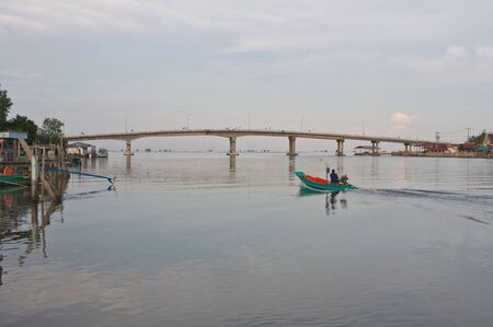 View of local fishing boat and bridge in Thailand photo