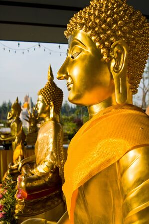 Face of golden buddha with yellow robe photo