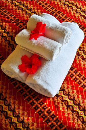 bedcover: Stack of white towels placed on red bedcover Stock Photo