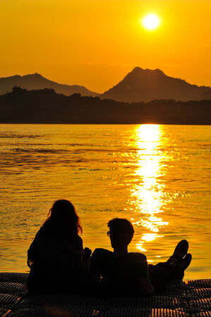 Two lovers are sitting watching the sunset photo