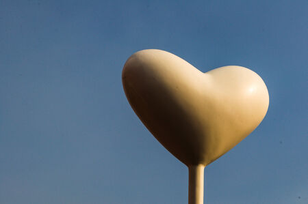 White heart balloon against blue sky photo