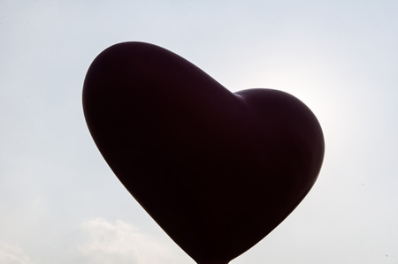 Silhouette of heart shape against blue sky photo