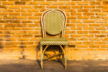 Vintage wooden chair near old brick wall photo