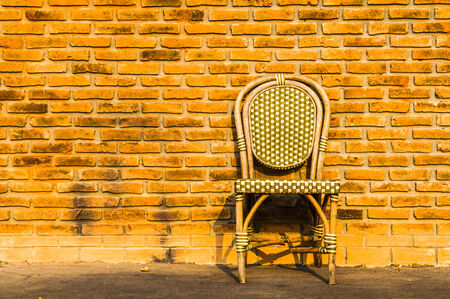Vintage wooden chair near old brick wall background photo
