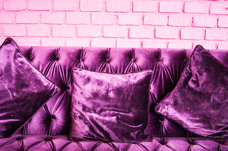 Vintage violet sofa and pink color of brick wall  photo