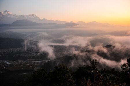 apogee: Morning sunrise and fog on the mountain in PokharaNepal
