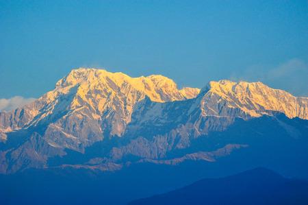 apogee: Orange of sunlight on the snow mountains peak of machapuchare in Pokhara,Nepal