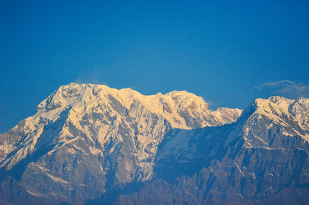 apogee: Sunlight effect on the big snow mountains against blue sky in PokharaNepal