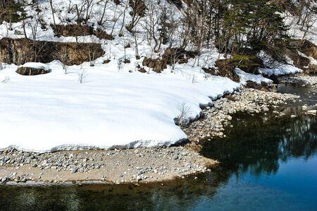 shirakawa go: Beautiful view of lake and snow on the stone in Shirakawa Go village, Japan