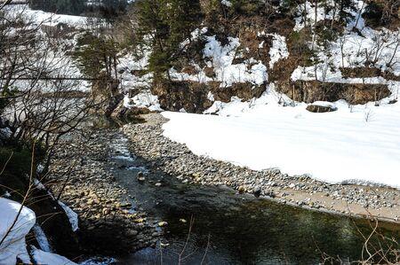 shirakawa go: Ice stream meandering through snow-covered grasses and bushes in the Shirakawa Go village ,Japan