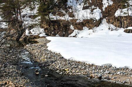 shirakawa go: Beautiful snow covered on the stream in Japan Stock Photo