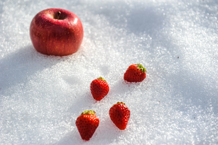 big apple: Strawberries and big apple on snow Stock Photo