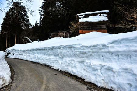 shirakawa go: Ancient house on the snow wall beside a country road in Japan Stock Photo