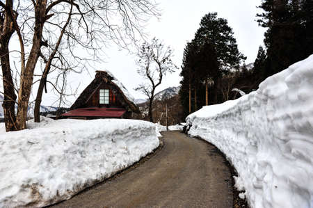 shirakawa go: Ancient house and snow wall beside a country road in Japan