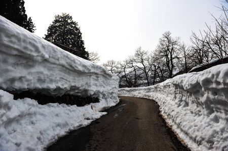 shirakawa go: The black road curved side walls of snow