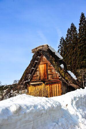 Prachtige oude houten huis tegen de blauwe hemel in het besneeuwde weer Redactioneel