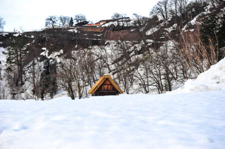 shrinkage: Triangle roof of old wooden house in the snowy forest of Japan
