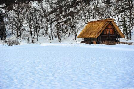 paisaje nevado y antigua casa de madera en el pueblo de Shirakawa Go, Japón Editorial