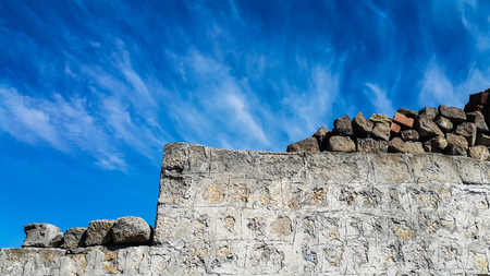 Old stone wall and blue sky Stock Photo