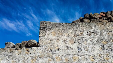 Ancient of block stone wall against blue sky