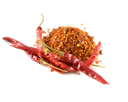 Dried red peppers and flakes, isolated on white.