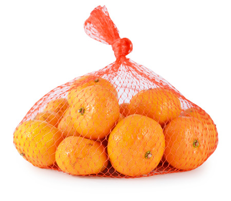 Fresh orange in plastic netting sack on white background photo
