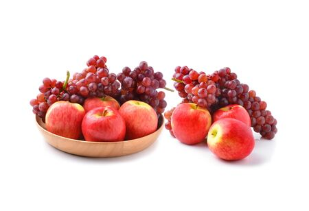 ripe red apples and grapes on white photo