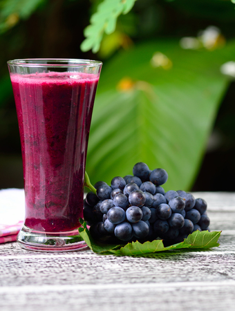 green and purple vegetables: Glass of Grape Juice smoothie on wooden background