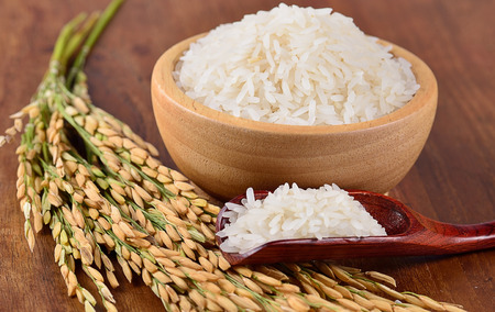 white rice on the wooden plate and rice plant , uncooked raw cereals