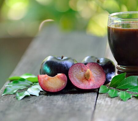 fresh plums juice on a wooden background