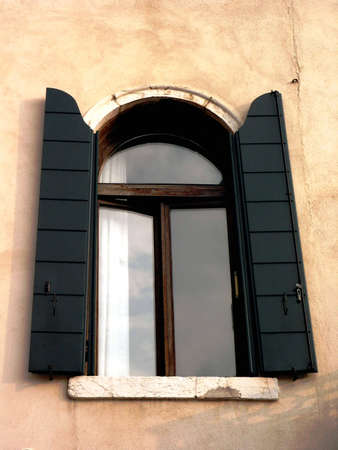 Old window with green shutters on the wall Stock Photo - 5538424