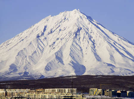 dormant: Dormant volcano covered with a snow and small northern town on Kamchatka