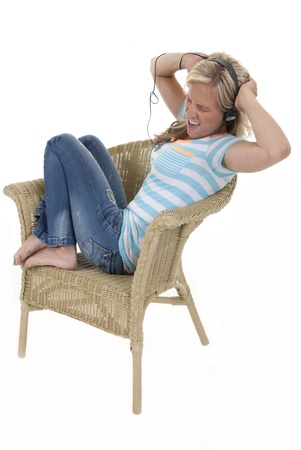 Attractive woman in striped shirt listening to music in chair  photo