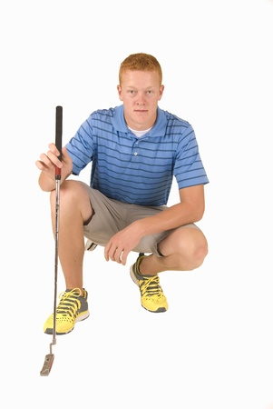 Attractive young man crouching with golf putter Stock Photo