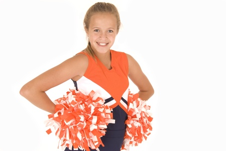 Young girl cheerleader standing with orange pompoms photo