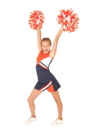 Young girl cheerleading with orange pompoms photo