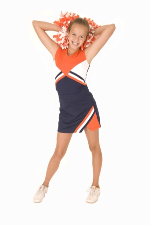 Young girl cheerleader standing orange white pomspoms Фото со стока