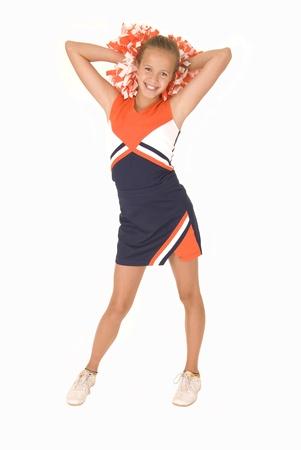 Young girl cheerleader standing orange white pomspoms Stock Photo