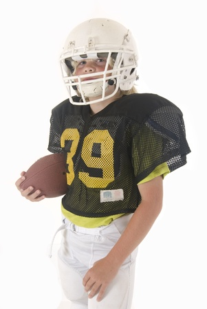 youth football: Boy fullback holding American football in uniform