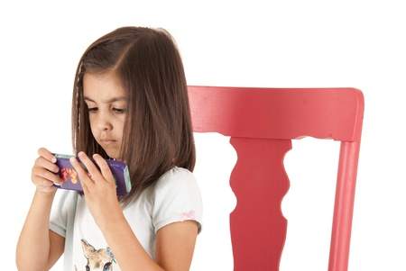 Young girl playing game on phone sitting Stock Photo