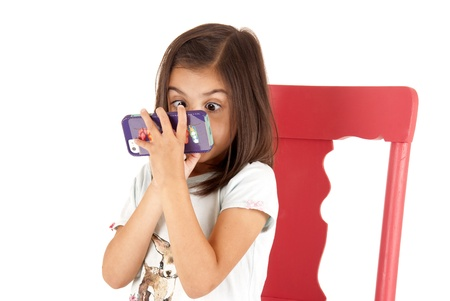 Wide eyed girl playing game on phone Stock Photo