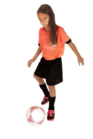 Girl in pink jersey kicking soccer ball Stock Photo