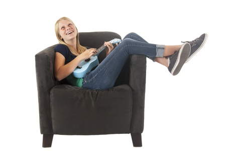 blonde teen playing a ukulele in chair Stock Photo - 21684040